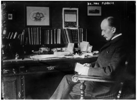 Imagen en blanco y negro de Max Planck mayor sentado en una silla delante de su escritorio, leyendo. Viste un traje y en el escritorio hay numerosos libros.